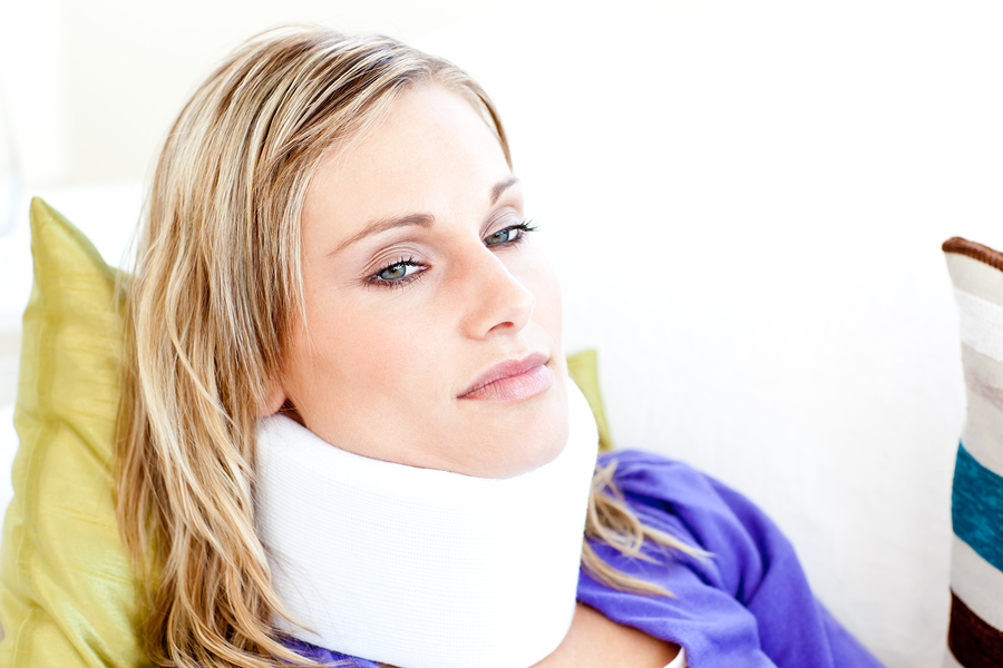 Beautiful woman wearing neckbrace lying on a sofa against a white background
